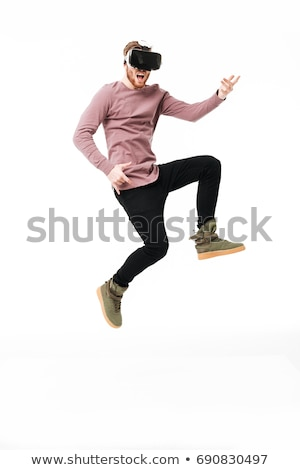 Cheerful bearded young man wearing virtual reality device Stock photo © deandrobot
