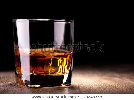 Glass of whiskey on dark background. Close up Stock photo © dashapetrenko
