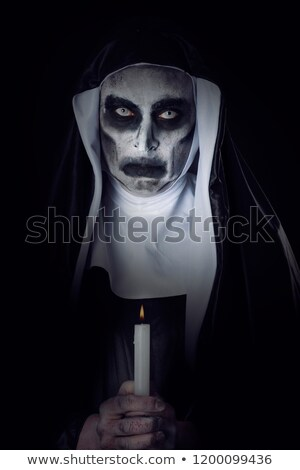 frightening evil nun with a lit candle stock photo © nito