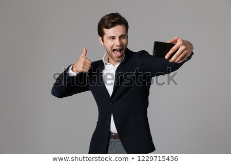 Image of joyous businessman 30s in formal suit showing thumb up  Stock photo © deandrobot