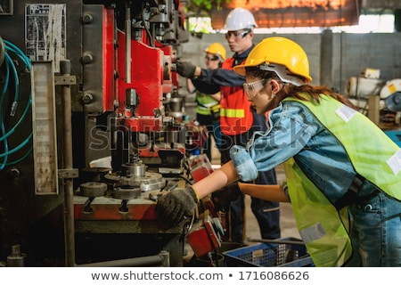 man and woman working together in metal workshop stock photo © kzenon