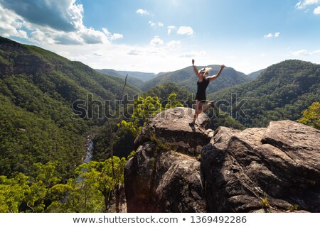 Spirited woman jumping on a high cliff ledge. Stock photo © lovleah