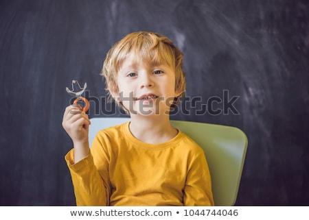 Three-year old boy shows vestibular plate. Plate with a bead to stimulate the tongue. dysarthria, rh Stock photo © galitskaya