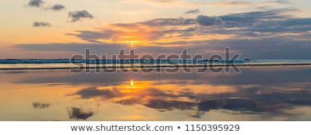 Panorama, Banner, long format of Sunset on the Kuta beach with reflection in the water on the island Stock photo © galitskaya