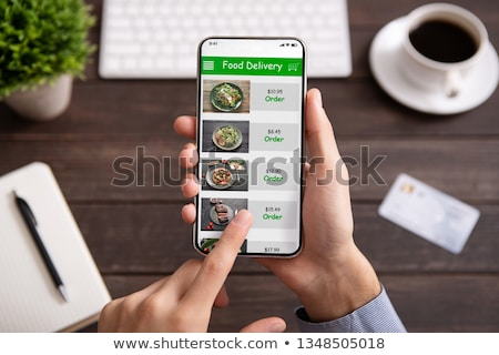 Young businessman scrolling in smartphone Stock photo © pressmaster