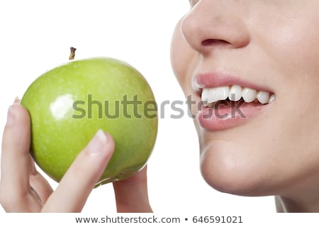 Stock photo: Closeup of the face of a woman eating a green apple, isolated ag