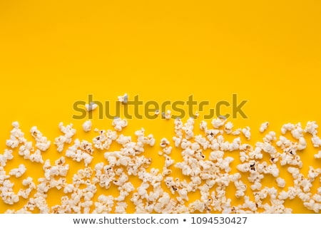 Scattered popcorn over yellow background Stock photo © neirfy