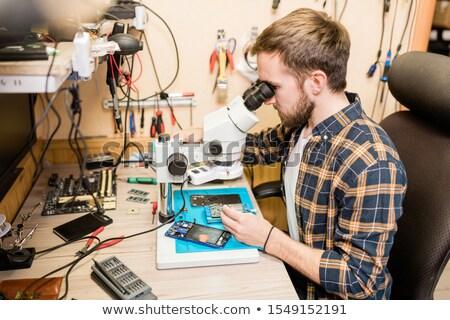 Szakállas szerelő ül asztal mikroszkóp lát Stock fotó © pressmaster