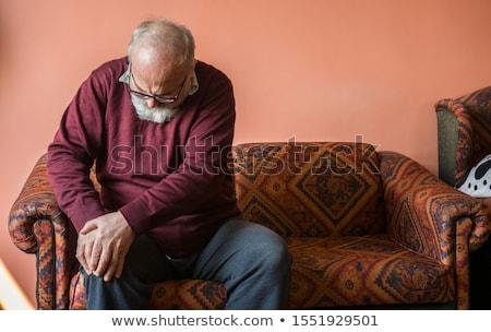 Adam diz ağrı oturma kanepe Stok fotoğraf © AndreyPopov