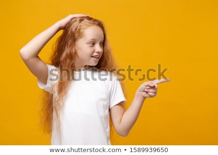 red haired teenage girl pointing finger up Stock photo © dolgachov