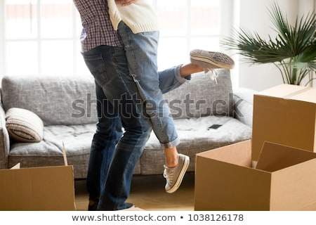 Couple in love purchase own house, embrace and stand closely to each other, hold keys from new apart Stock photo © vkstudio