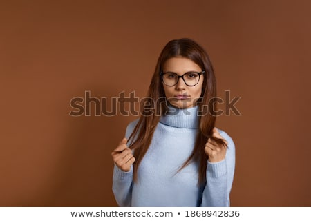 Thoughtful dark haired European female in spectacles looks aside, leans at back of couch, contemplat Stock photo © vkstudio