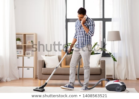 man with vacuum cleaner calling on cell at home Stock photo © dolgachov