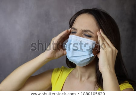 Young woman wearing face medical mask have headache, infected by virus, healthcare concept Stock photo © robuart