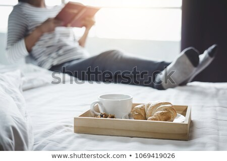 Morning Cup Of Coffee And Croissant On The Bed With Old Book Сток-фото © Freedomz