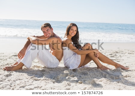 Portrait of young couple sitting together on sand on beach and l stock photo © HASLOO