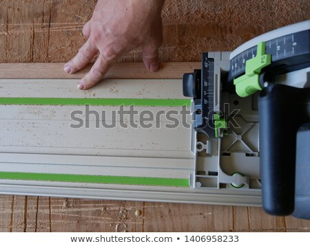 Laborer with saw sitting on a workbench Stock photo © photography33