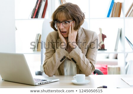 Scared woman at her office desk  Stock photo © stokkete