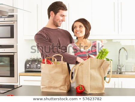 Young Couple Unpacking Shopping In Modern Kitchen Stock photo © monkey_business
