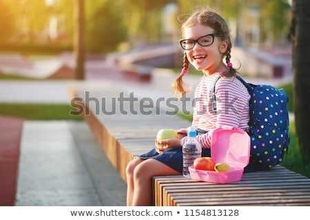 young schoolgirl standing eating an apple stock photo © stryjek
