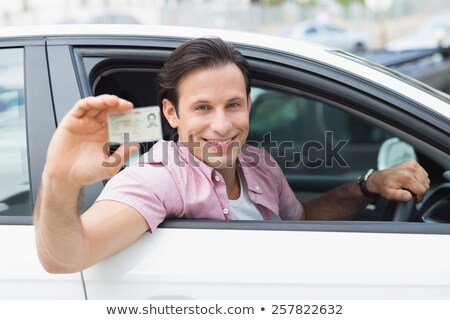 driver smiling sitting in car and showing drivers license Stock photo © vladacanon