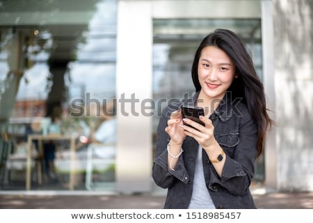 smiling businesswoman with smartphone in office stock photo © dolgachov