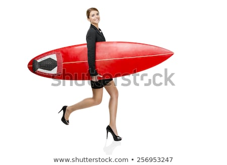 Smiling surfer girl holding her surfboard and jumping on the bea Stock photo © wavebreak_media