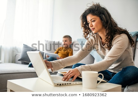 Business woman using her mobile phone and drinking coffee. Stock photo © nenetus