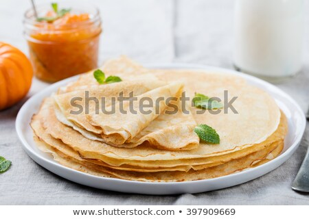 Stock fotó: Thin Crepes Or Pancakes With Fresh Pumpkin Confiture Jam And Bottle Of Milk On A Rustic Wooden Back