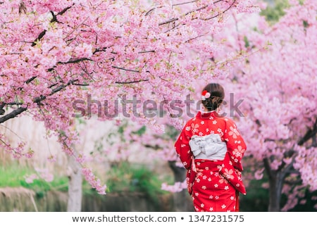 Smiling woman standing in blooming garden Stock photo © deandrobot