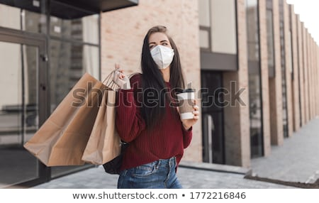 Happy young women with shopping bags walking in the street Stock photo © deandrobot