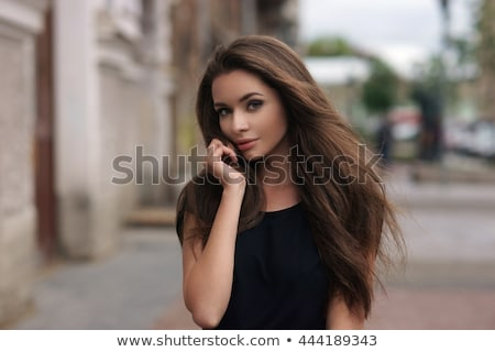 Beautiful brunette woman with long hair and black dress Stock photo © deandrobot