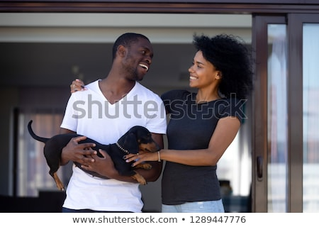 Foto stock: Cheerful African Man Playing With Dog And Laughing Outdoors