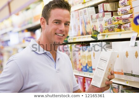 Stock photo: The young man, choosing camera in the department of household ap