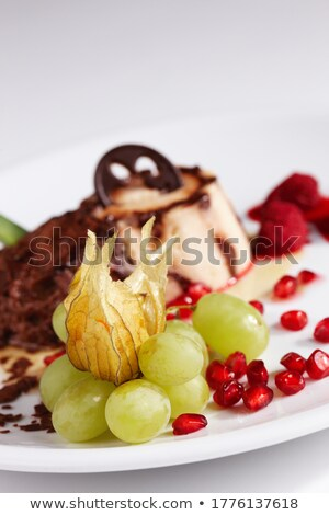 Sweet dessert - chocolate and vanilla pudding with grapes and nu Stock photo © Yatsenko