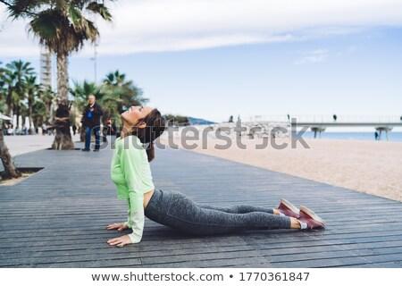 Full length of woman practicing cobra pose at beach stock photo © wavebreak_media