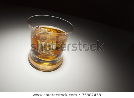 Glass of Whiskey and Ice Under Spot Light. Stock photo © feverpitch