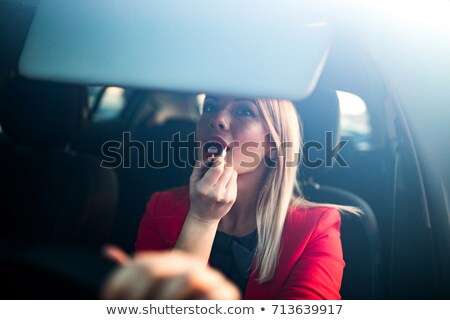 Stock photo: Young woman putting lipstick in car