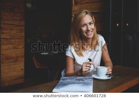 smiling pensive woman sitting by the table in cafe stock photo © deandrobot