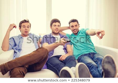три · друзей · гостиной · Смотря · телевизор · улыбаясь · человека - Сток-фото © monkey_business