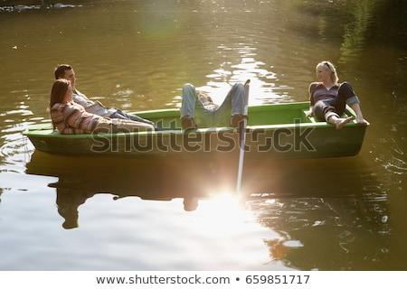 Négy barátok evezős csónak mosolyog fa kommunikáció Stock fotó © IS2