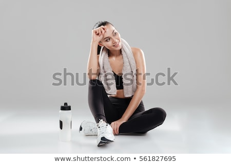 Beautiful young fitness woman sitting with towel and water. Stock photo © deandrobot