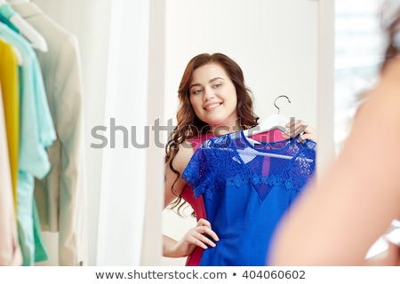 happy plus size woman in dress looking at mirror stock photo © dolgachov