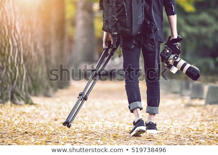 Stock photo: Photographer with Tripod on Background of Pictures