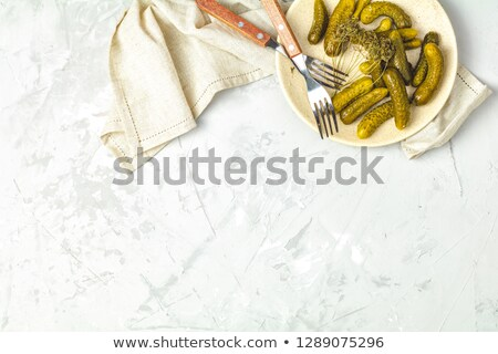Stock photo: Pickled gherkins or cucumbers in plate on light gray concrete su