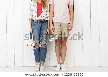 Cropped photo of amusing couple man and woman painting white wal Stock photo © deandrobot