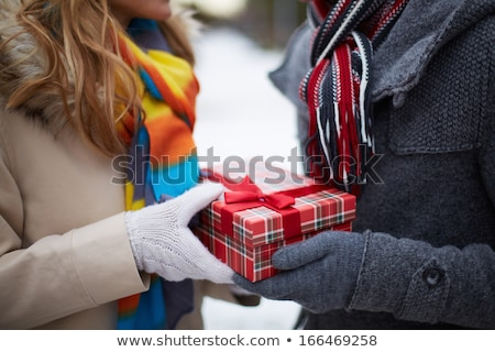 close up of couple hands with christmas gift box stock photo © dolgachov