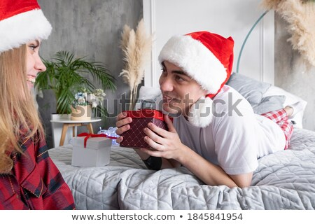 smiling woman in pajama holding gift box and looking at the camera valentines day concept stock photo © elenabatkova