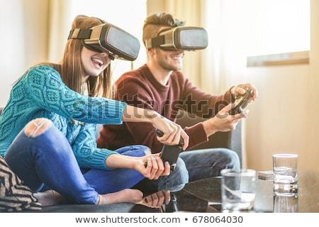 ストックフォト: 若い男 · 演奏 · ビデオゲーム · バーチャル · 現実 · 眼鏡