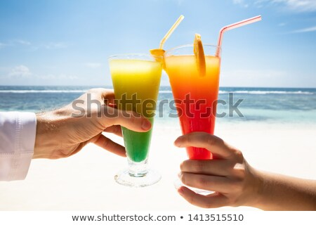 Couple's Hand Toasting The Cocktail Glasses In Front Of Sea Stock photo © AndreyPopov